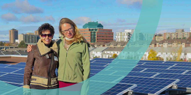 OREC Members posing in front of a community-owned solar power project